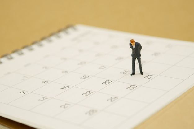 Miniature people businessmen standing on white calendar Premium Photo