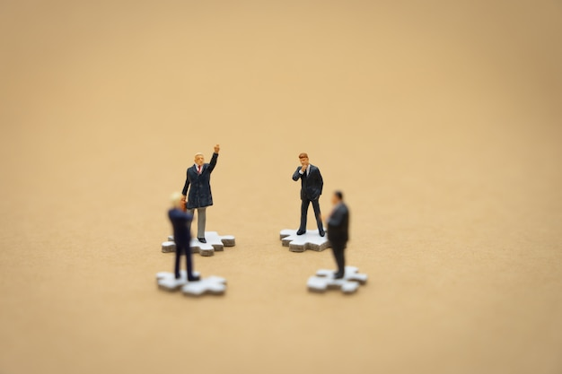 Miniature people businessmen standing on white jigsaw Premium Photo
