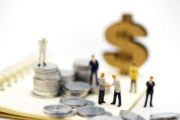 Miniature people,  businessmen standing with coins stack, finance and investment concept. Premium Photo