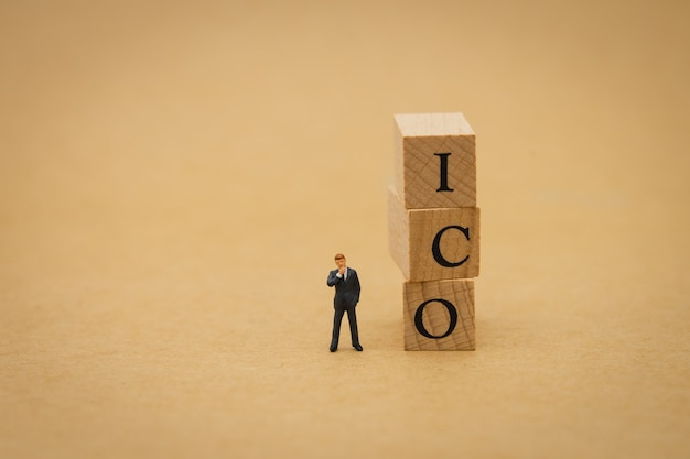 Miniature people businessmen standing with wood word ico (initial coin offering) Premium Photo