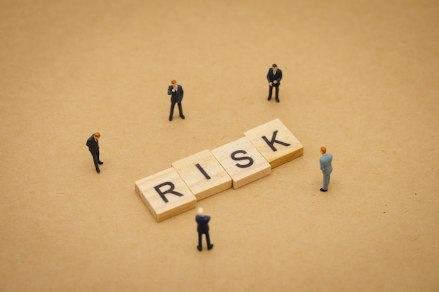 Miniature people businessmen standing with wood word risk Premium Photo