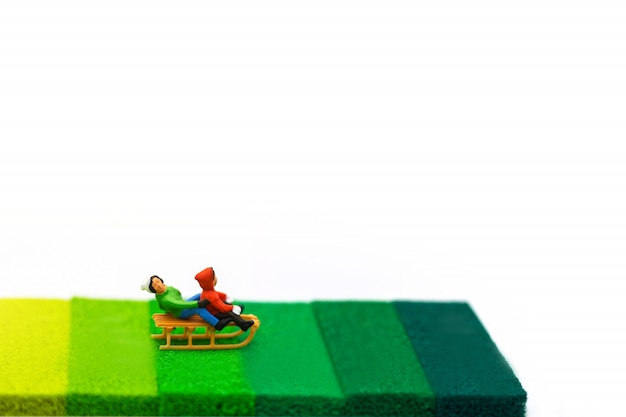 Miniature people, childrens playing fun with snow slider Premium Photo