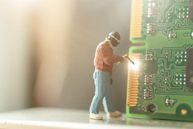 Miniature people : computer repairman repair computer hardware Premium Photo