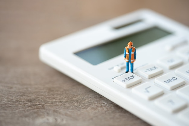 Miniature people construction worker keypad tax button for tax calculation. Premium Photo