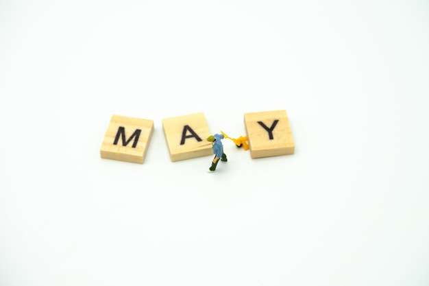 Miniature people construction worker standing with wood word month. Premium Photo