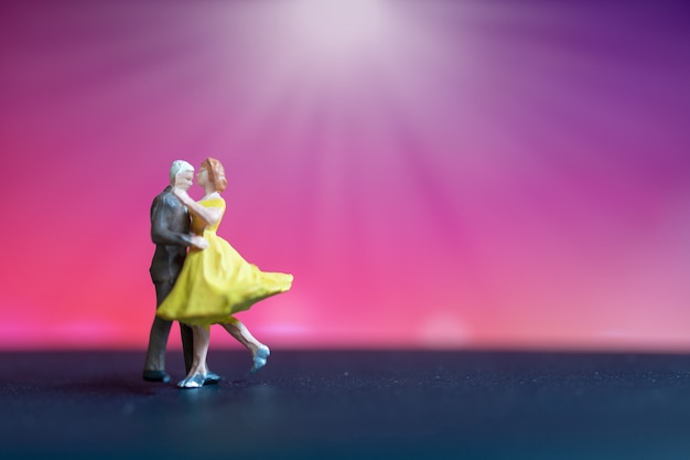 Miniature people, couple dancing with colorful  background Premium Photo