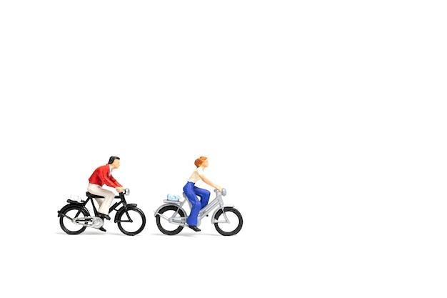 Miniature people: couple ride bicycle on white background Premium Photo