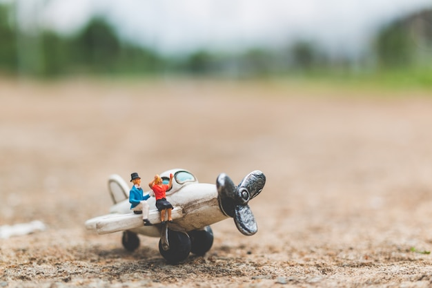 Miniature people: couple sitting on the airplane Premium Photo