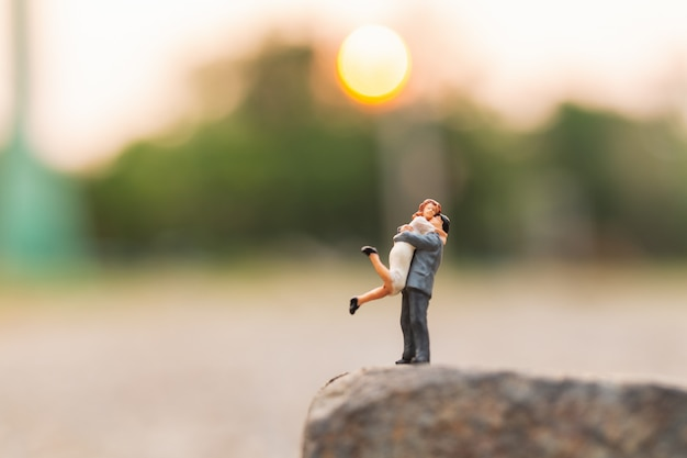 Miniature people : couple standing on the rock cliff Premium Photo