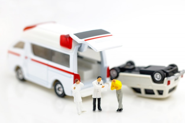 Miniature people: doctor and patient standing with ambulance. Premium Photo