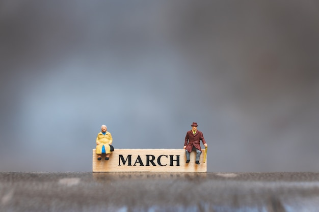 Miniature people, elderly man and woman sitting on march wooden calendar Premium Photo