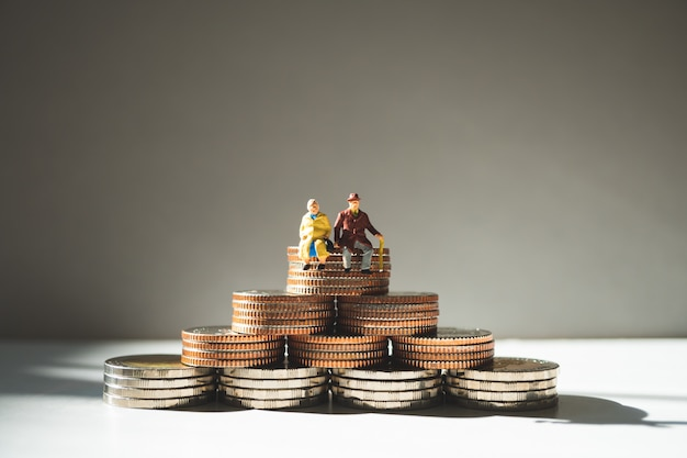 Miniature people, elderly people sitting on stack coins using as job retirement concept Premium Photo
