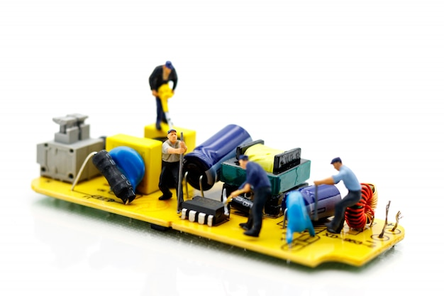 Miniature people: engineers fixing error on chip of circuit board. computer repair concept. Premium Photo
