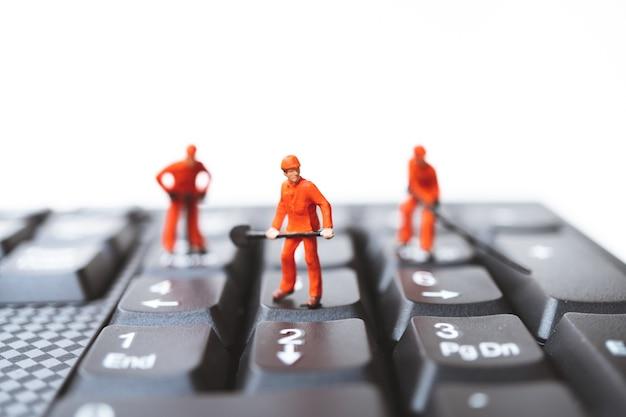 小型の人々、エンジニアチームがコンピュータのキーボードに立っている Premium写真