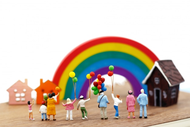 Miniature people: family and children enjoy with colorful balloons. Premium Photo