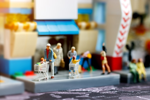 Miniature People Family With Shopping Cart In Supermarket Premium Photo