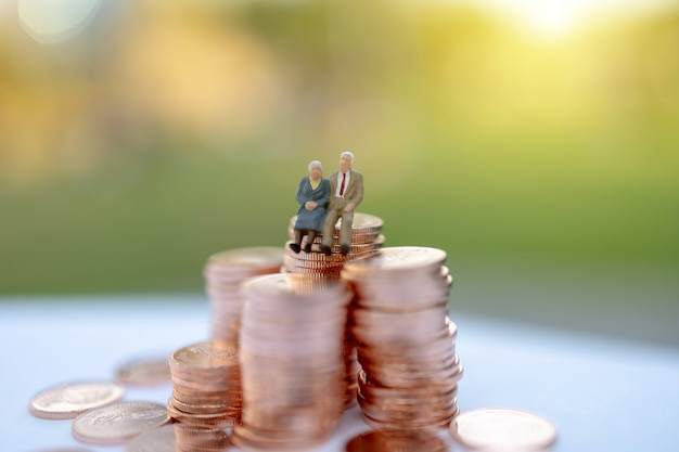 Miniature people: happy old people sitting on coins stack, retirement  and life insurance concept. Premium Photo