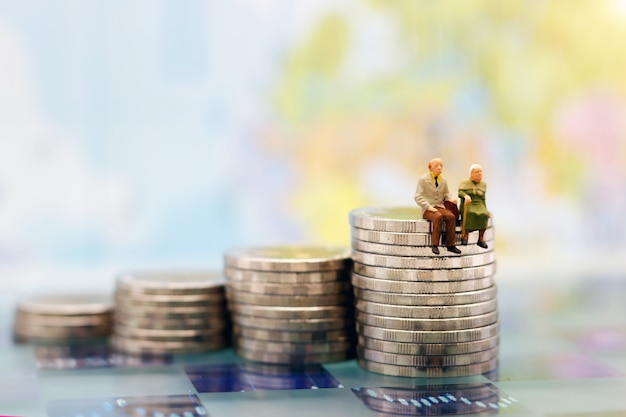 Miniature people: happy senior couple sitting on coins stack, retirement concept. Premium Photo