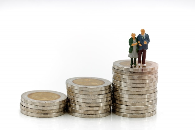 Miniature people: happy senior couple standing on coins stack. concept of retirement. Premium Photo