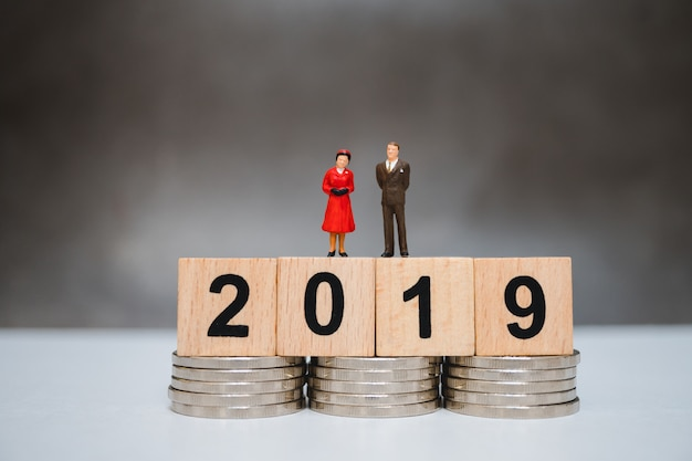 Miniature people, husband and wife standing on wooden year 2019 and stack coins Premium Photo