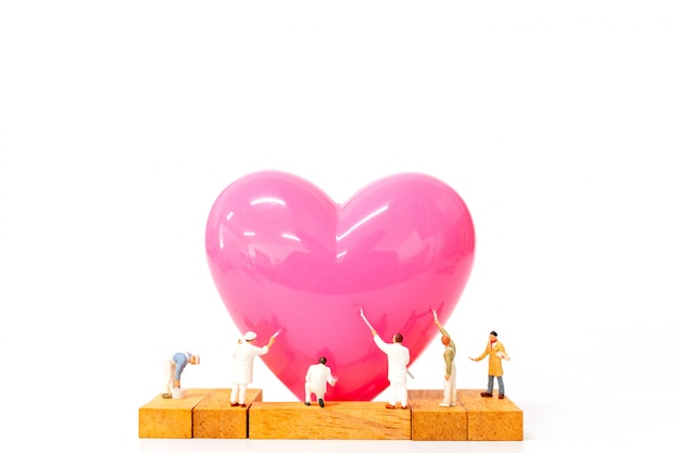 Miniature people painting pink heart on  white background Premium Photo