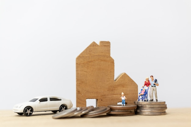 Miniature people : parents with children with house and coins stacking Premium Photo