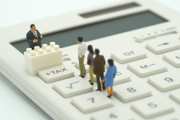 Miniature people pay queue annual income (tax) for the year on calculator. Premium Photo