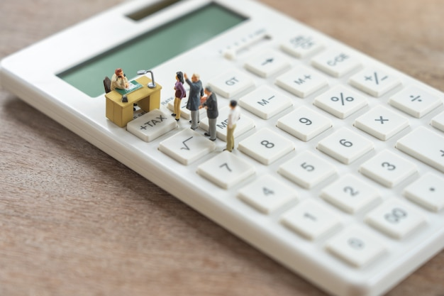 Miniature people pay queue annual income tax for the year on calculator. Premium Photo