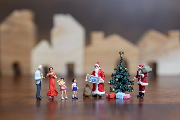 Miniature people: santa claus and happy family Premium Photo