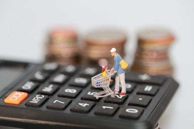 Miniature people: shopper and trolley walking on calculator with blur coins behind Premium Photo