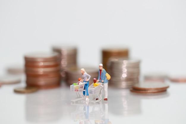 Miniature people: shopper walking beside money, business using as background Premium Photo