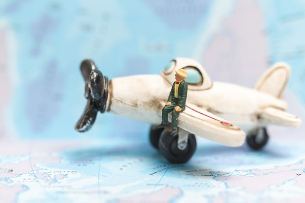 Miniature people sitting on the airplane with world map background Premium Photo