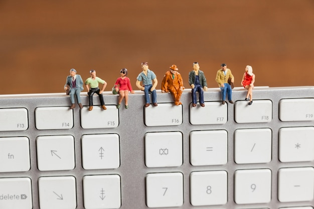 Miniature people sitting on top of keyboard Free Photo