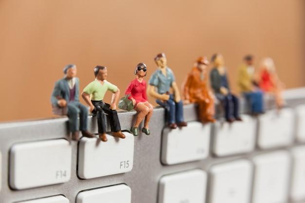 Miniature people sitting on top of keyboard Free Photo