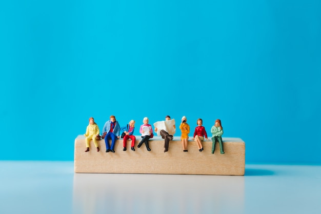Miniature people sitting on wooden block with on blue background Premium Photo