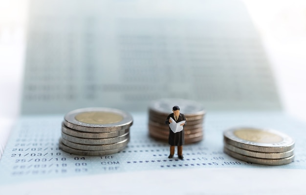 Miniature people stand on the bank passbook and coins stack, retirement concepts. Premium Photo