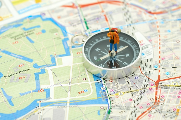 Miniature people standing travel planner on a compass with japan map Premium Photo