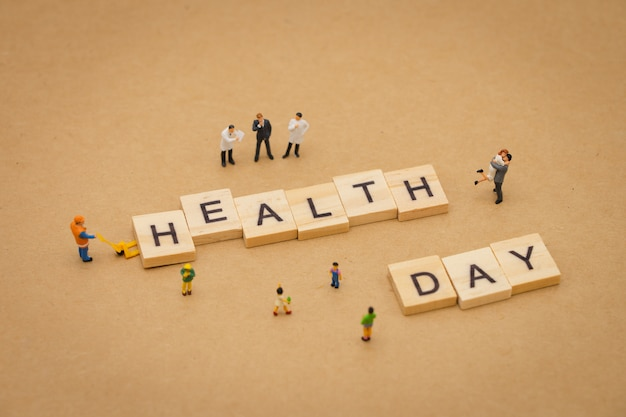 Miniature people standing with wood word health day using as background universal day Premium Photo