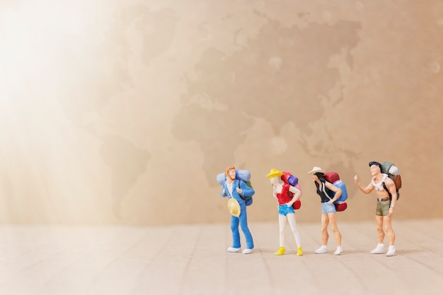 Miniature people : traveler with backpack walking on the map Premium Photo