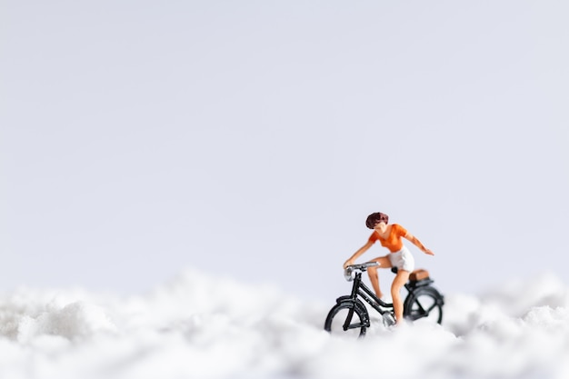 Miniature people : travelers riding a bicycle on snow Premium Photo