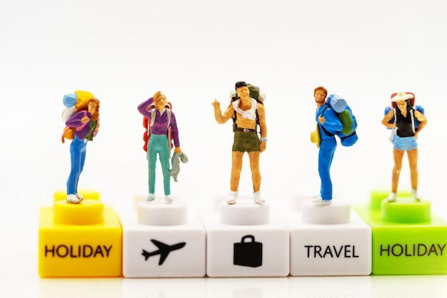 Miniature people: traveller with backpack stading on podium with text Premium Photo