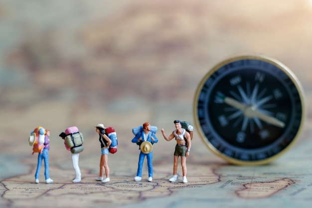 Miniature people: traveller with backpack standing on vintage map. Premium Photo