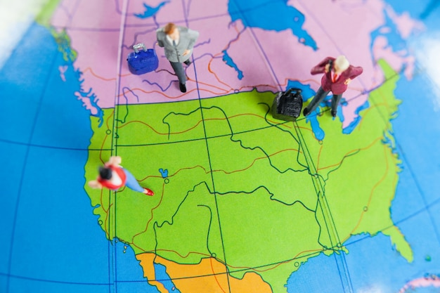 Miniature people travelling on globe Free Photo