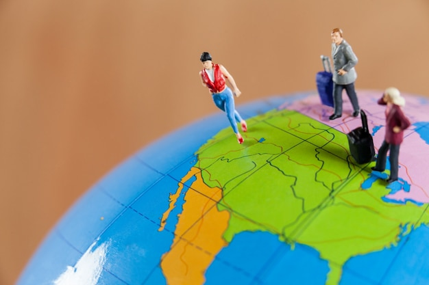 Miniature people travelling on globe Free Photo