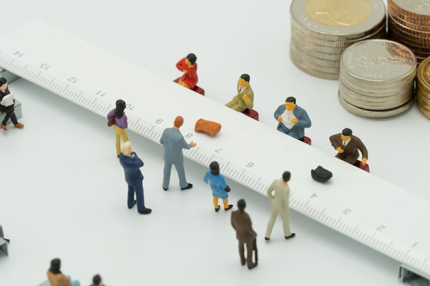 Miniature people use cash deposit. at the bank counter or financial institution. Premium Photo