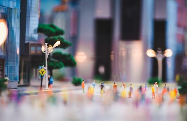 Miniature people walking on streets, people are moving across the pedestrian crosswalk Premium Photo