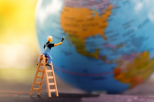 Miniature people: worker cleaning world map. Premium Photo