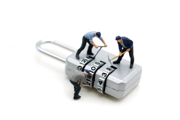 Miniature people: worker hacking in  padlock security. Premium Photo