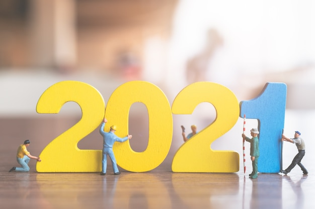 Miniature people : worker team build wooden number 2021  , happy new year concept Premium Photo