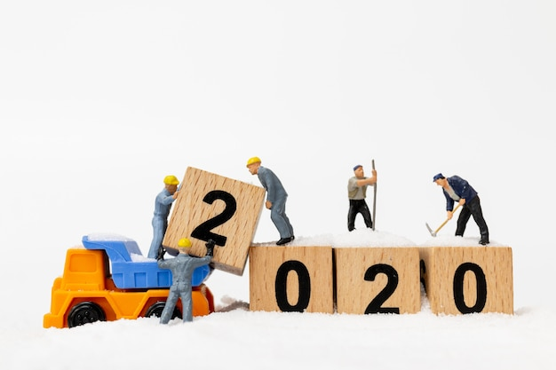 Miniature people, worker team create wooden block number 2020 Premium Photo